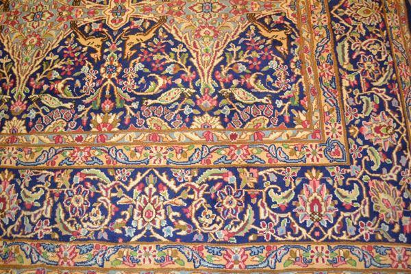Grande tappeto, Kirman, Persia, 1920 circa, fondo azzurro decorato da motivi romboidali tra tralci vegetali e volatili nei toni del rosa, azzurro e blu, cm 300x356