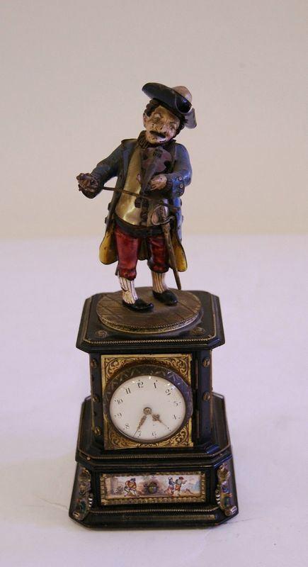 Originale orologio, con quadrante sormontato da figura di gobbo realizzato in madreperla e metallo a smalti policromi, poggiante su base, con placchette in smalti a scenette di genere, alt. cm 22, danni