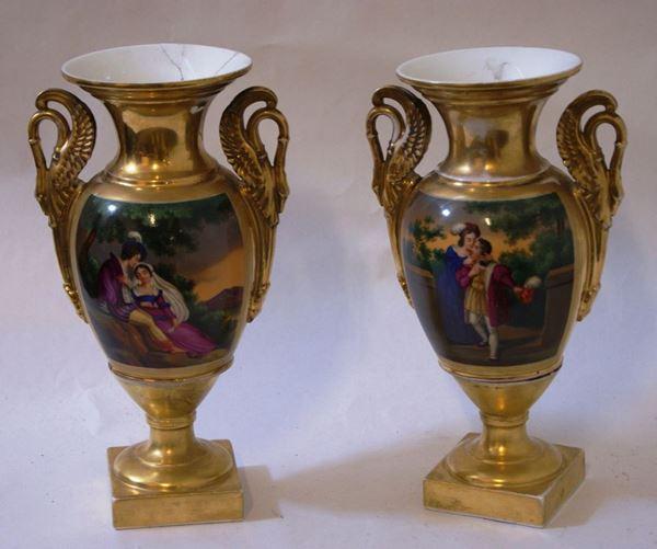 Coppia di vasi, Francia, sec. XIX, in porcellana decorata a figure, con manici a forma di cigno, cm 32  uno restaurato(2)