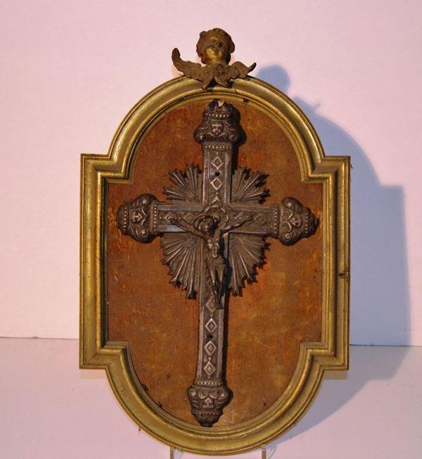 Crocefisso in metallo argentato, secolo XIX, montato su pannello entro cornice in bronzo dorato, cm 30x20