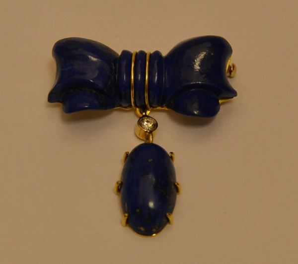 Spilla a forma di fiocco, in oro giallo e lapislazzuli, con brillantino di ct. 0,26, peso oro g 5,7, marcato Torrini