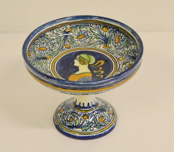Alzata, Faenza, sec. XX, decorata a motivi vegetali e centralmente un profilo di donna, alt, cm 16,5, diam. cm 20