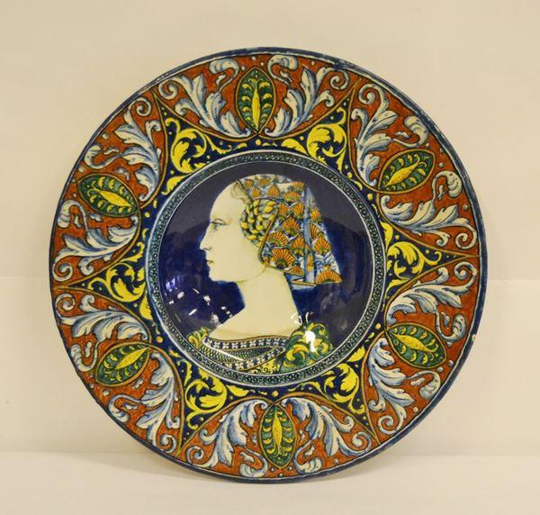 Piatto, Faenza sec. XX, in maiolica, decorato a motivi vegetali e centralmente un profilo di donna, diam. cm 43,5
