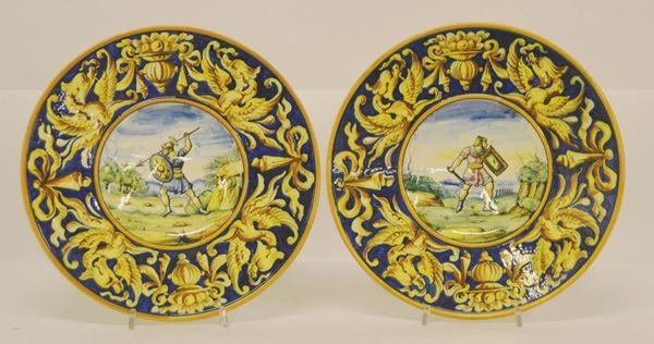 Coppia di piatti, sec. XX, in maiolica, decorati a GUERRIERI, diam. cm 27 (2)