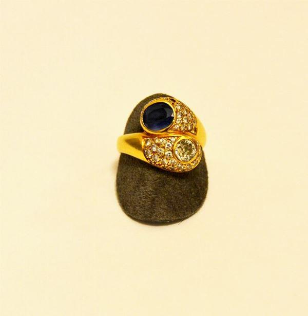 Anello in oro giallo a  contrariè  con brillante di circa ct 0,35 ,zaffiro , e pavè di brillantini g 12,3