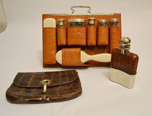 Set da viaggio, composto da: cinque contenitori in vetro con tappi in argento, due spazzole, sec. XX, bottiglia porta liquori e borsetta in pelle, inizi sec. XX   (9)