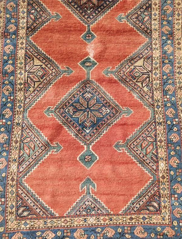 Tappeto Kazak, sec. XX, fondo nei toni del rosso e dell'azzurro, a motivi