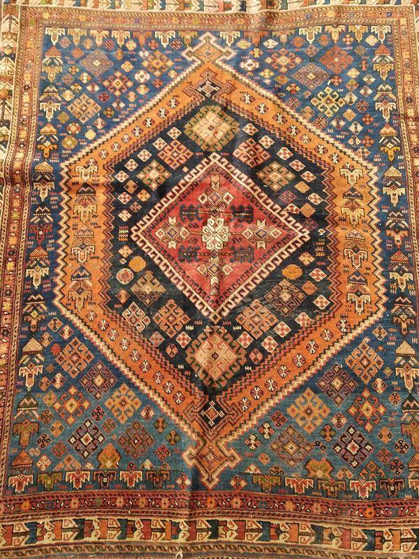 Piccolo tappeto, sec. XX, fondo rosso a motivi geometrici, cm 97x126